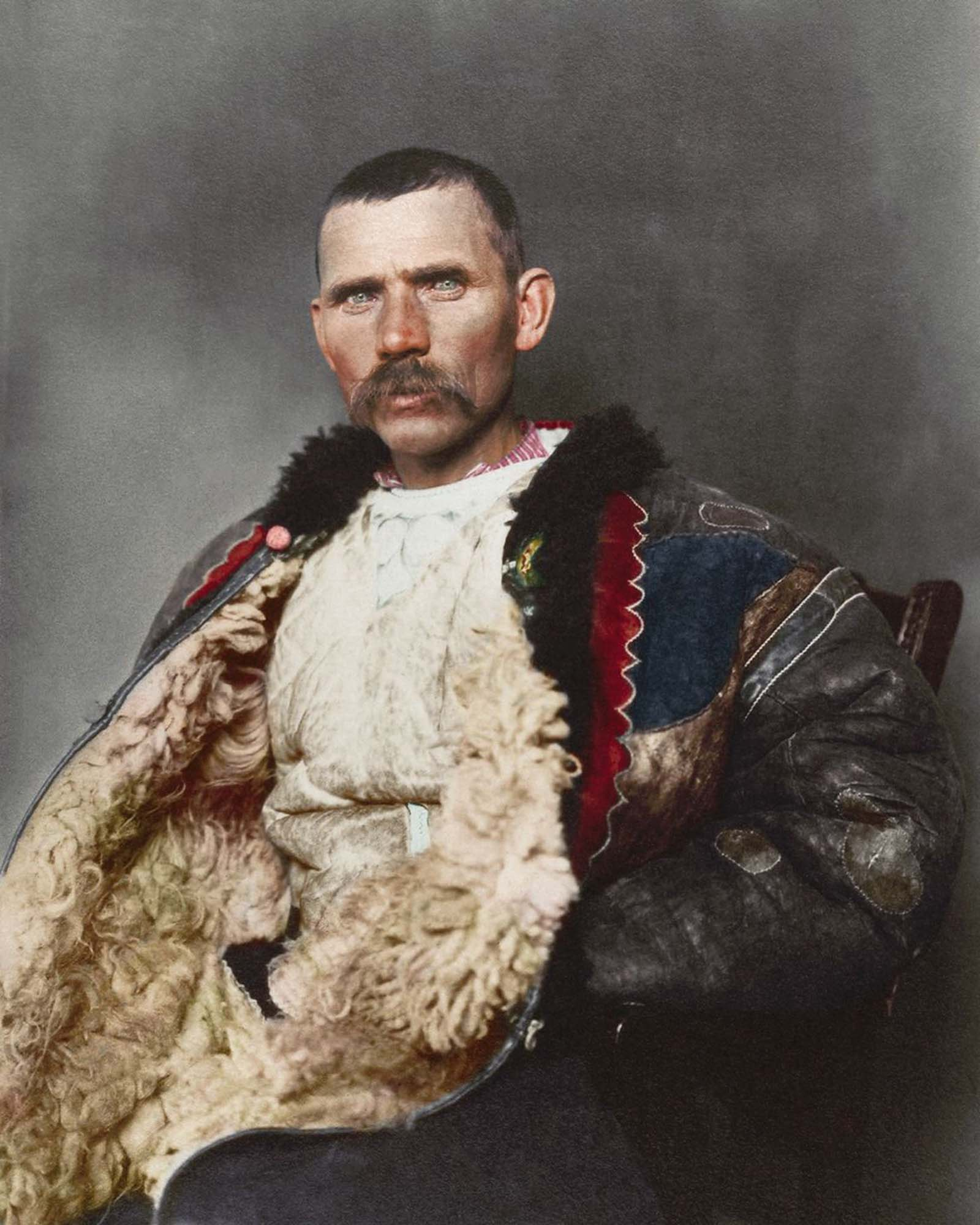 """Romanian shepherd."""" Dominating the photograph is a traditional shepherd's cloak known as sarică, made from three or four sheepskins sewn together with the fleece facing outwards and generally extended to below the knee, which could be used as a pillow when sleeping outdoors. Sheepskin was also used"""