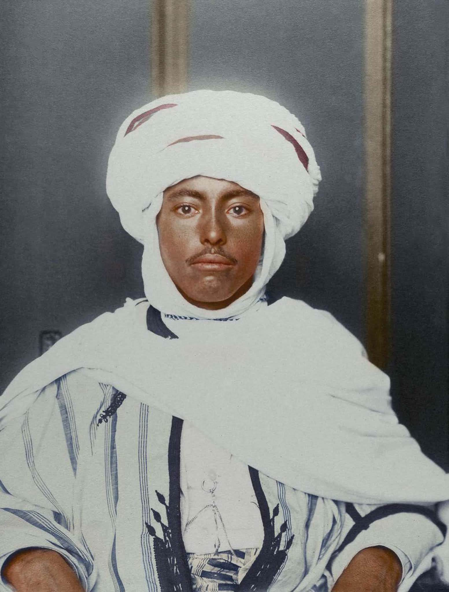 """Algerian man."""" It is noted that Algerian identity is shaped by its indigenous Berber, Arab, African and Mediterranean cultures. The kufiya is a square of fabric folded into a triangle and set upon the head by an 'iqual – a circlet of camel hair. The kaftan tunic has been worn by many cultures and wa"""