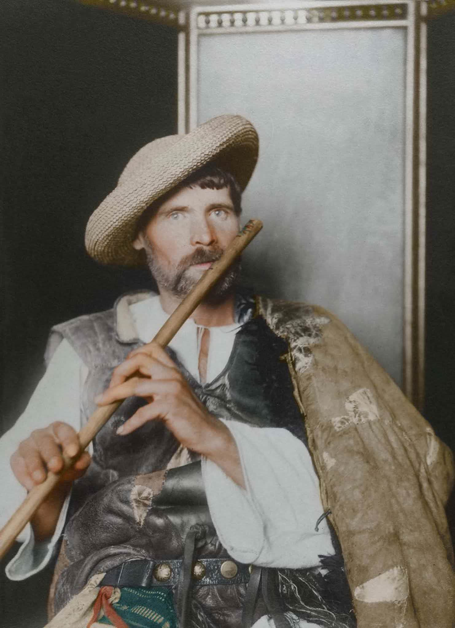 """Romanian piper."""" This particular cojoc, an embroidered sleeved sheepskin coat, is much plainer than the shepherd's version, making it a more practical, work-oriented coat, suggesting that the subject is of the working class given the lack of decoration and the straw hat. The waistcoat, known as a pi"""