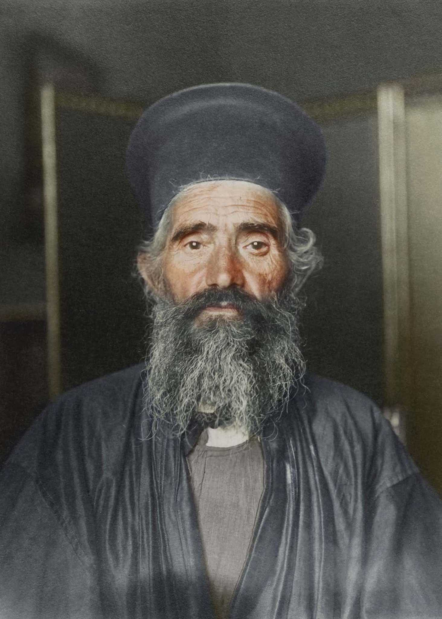 """Rev. Joseph Vasilon, Greek-Orthodox priest."""" The vestments of the Greek Orthodox church have remained largely unchanged. In this photograph, the priest wears an anteri, an ankle-length cassock (from the Turkish quzzak, from which the term 'Cossack' also derives) worn by all clergymen over which an a"""