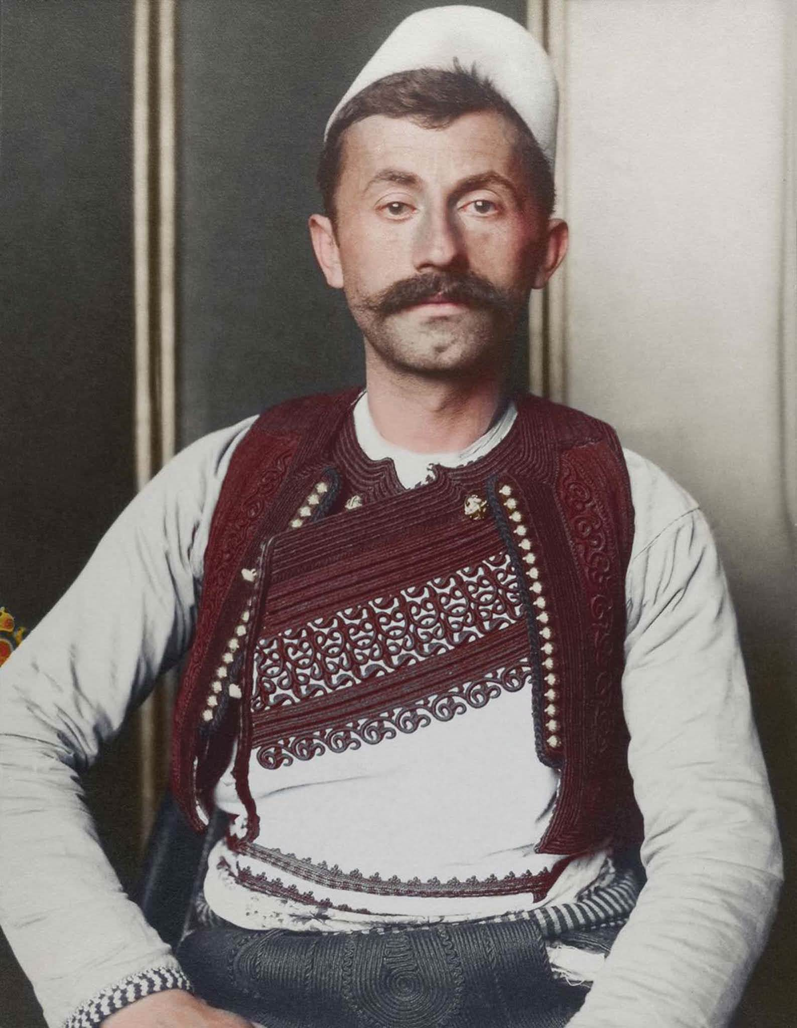 """Albanian soldier."""" The truncated brimless felt cap is known as a qeleshe, whose shape was largely determined by region and molded to one's head. The vest, known as a jelek or xhamadan, was decorated with embroidered braids of silk or cotton. Its color and decoration denoted the region where the wear"""