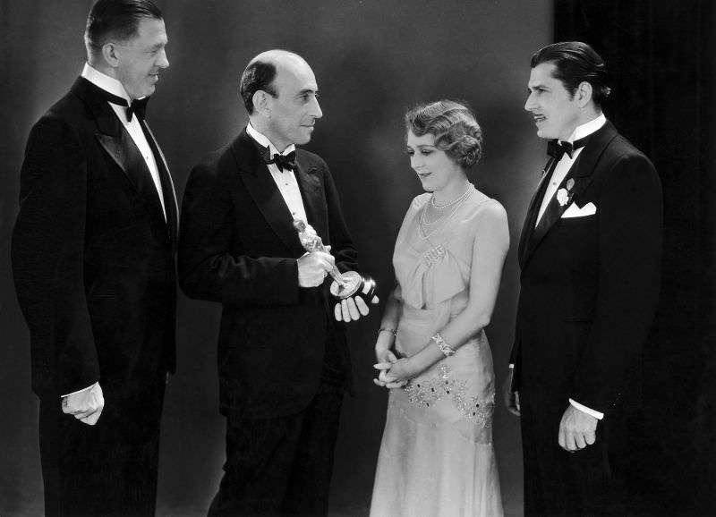William C Demille, President Of The Academy Of Motion Picture Arts And Sciences hands an Oscar to Mary Pickford (with Warner Baxter and Hans Kraly looking on) at the first ceremony in 1929