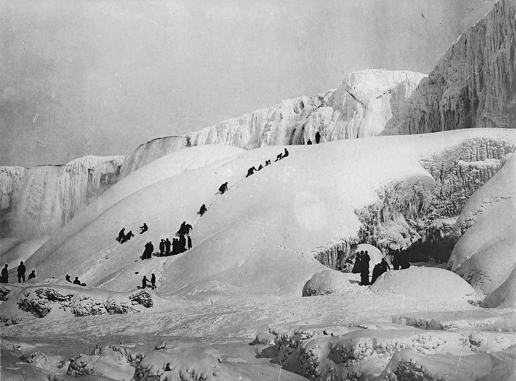 Frozen Niagara Falls with people gamboling over the ice, 1919.