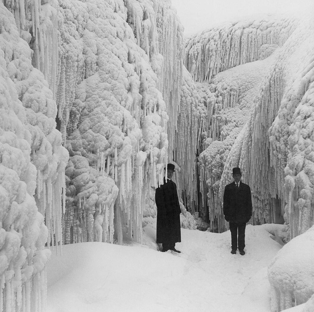 Two men pictured standing among the crystal corridors and caves of a frost-bound Niagara, 1950.