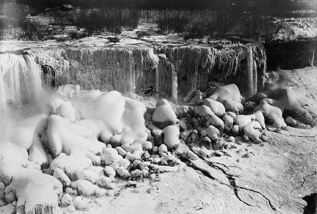A Bell Aircraft helicopter flies close to Niagara Falls, which is frozen. Only a trickle of water is coming from the falls, 1951.