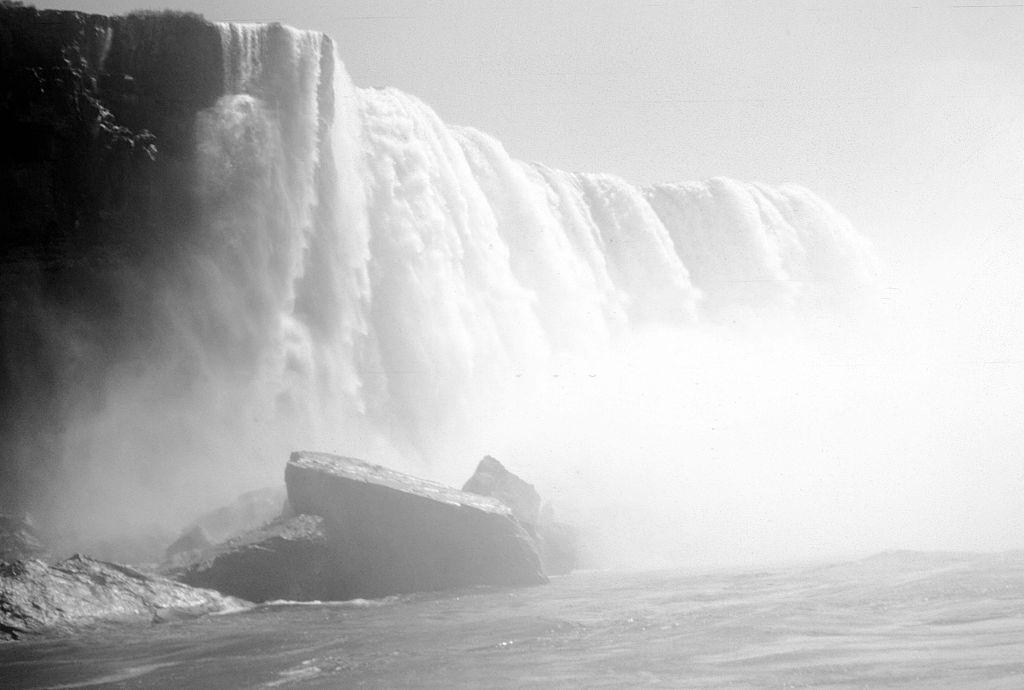 Niagara falls, viewed from a tourist boat, the water of the falls throwing up mist, 1953.