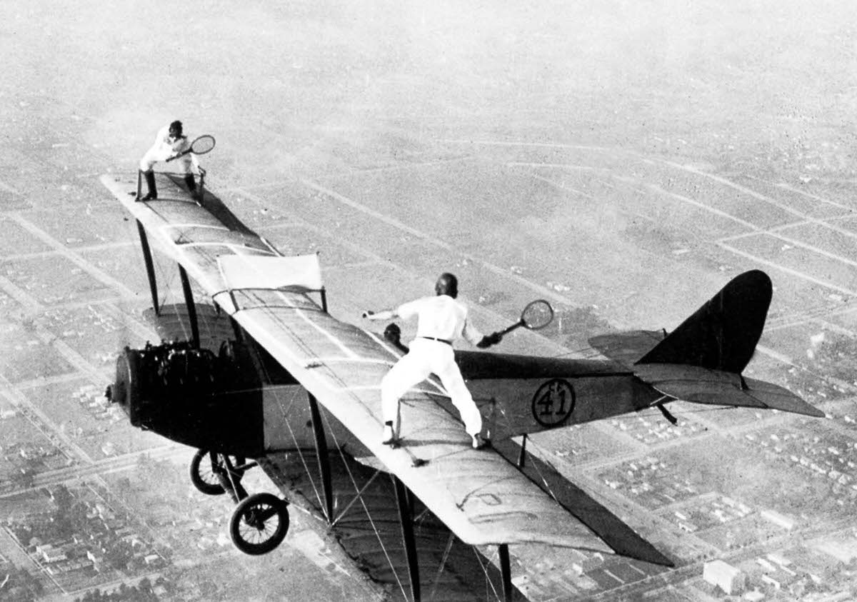 Ivan Unger and Gladys Roy play tennis on top of a biplane, 1925.