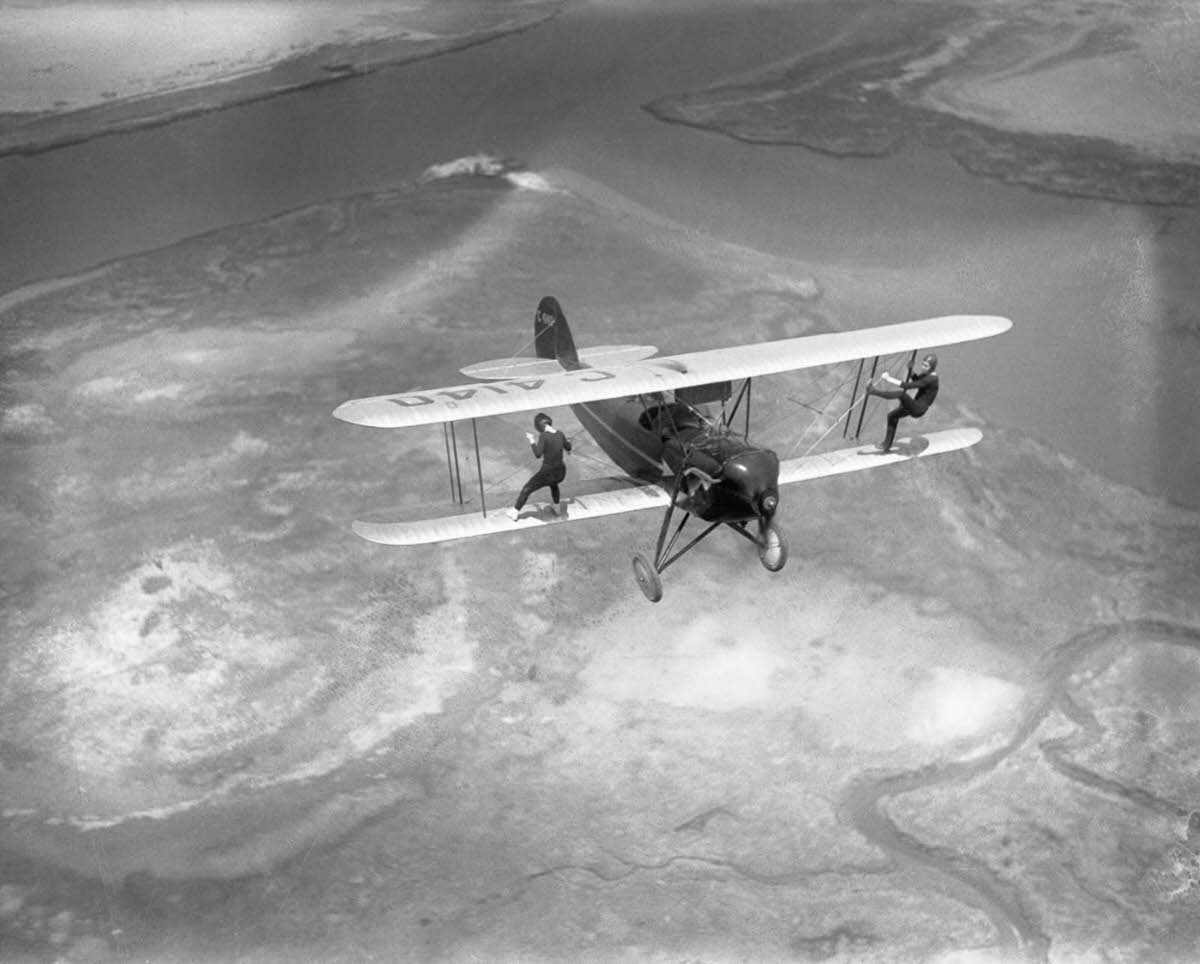Billy Bomar and Uva Kimmey of the Howard Flying Circus wing-walk on a biplane over New York State, 1930.