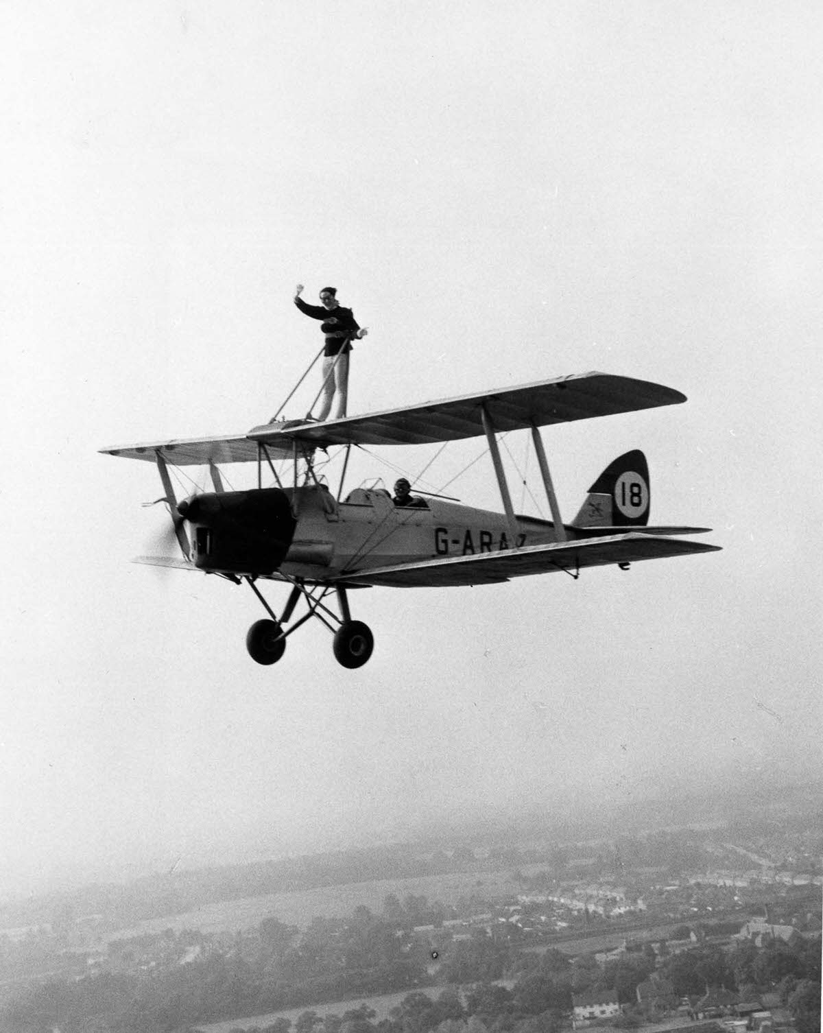 Juanita Jover takes a ride strapped to the wings of her boyfriend, stunt pilot Lewis Benjamin's Tiger Moth biplane, 1962.