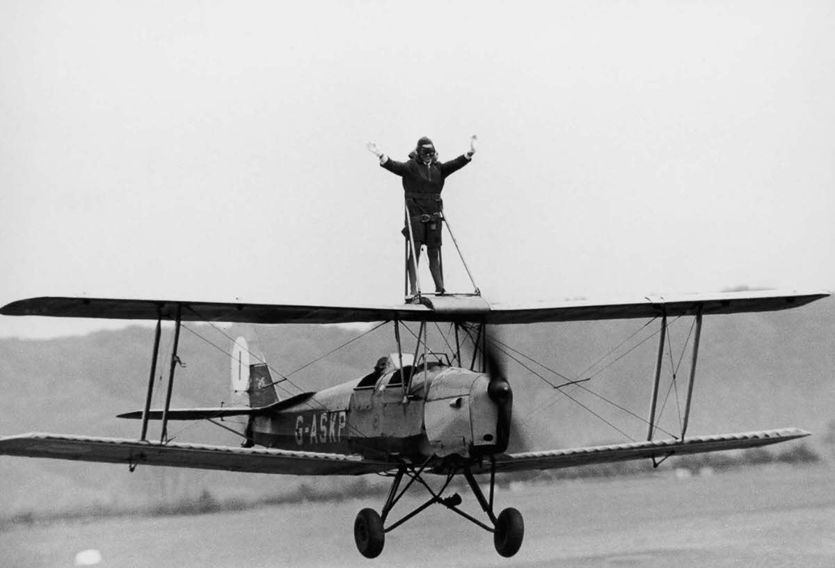 Jacqui Cheesman rides the wing of a Tiger Moth biplane at Wycombe Air Park, Buckinghamshire, England, 1968.