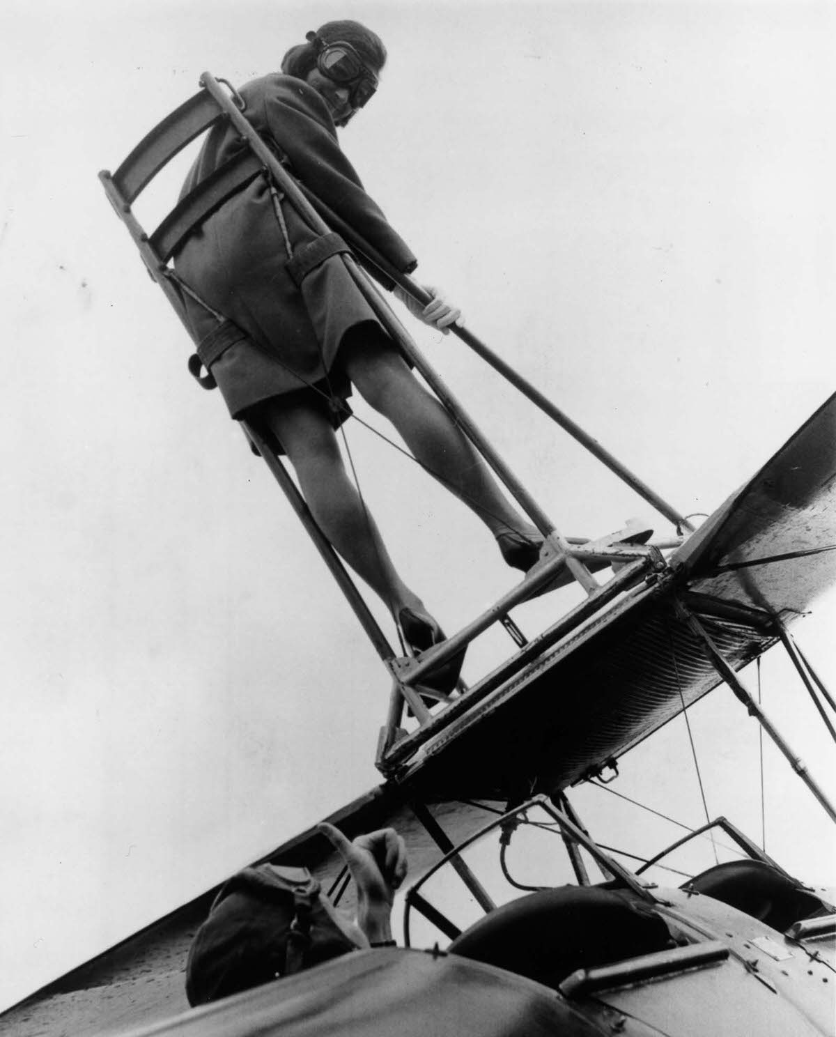Moira Boyd strapped onto the wing of a Tiger Moth biplane at Wycombe Air Park. 1968.