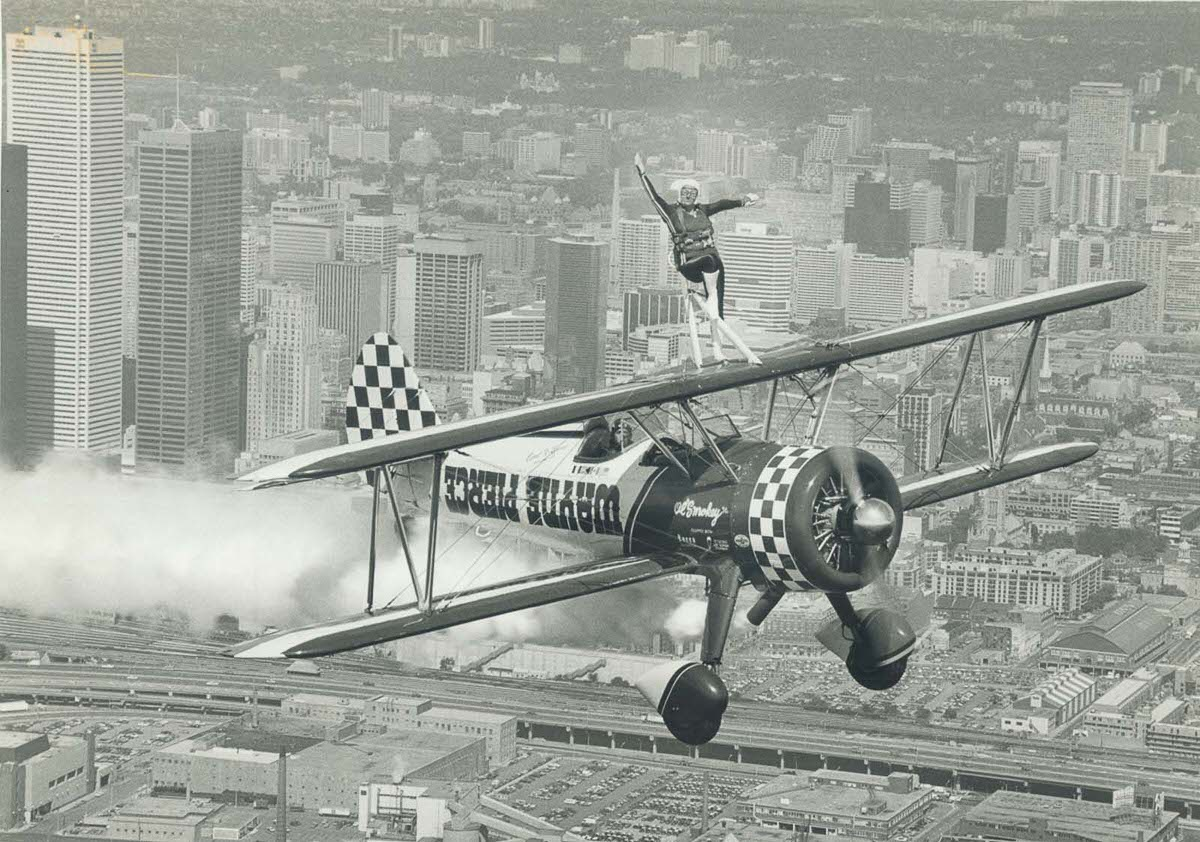 Carol Lynne rides atop a biplane piloted by her husband over Toronto, 1982.