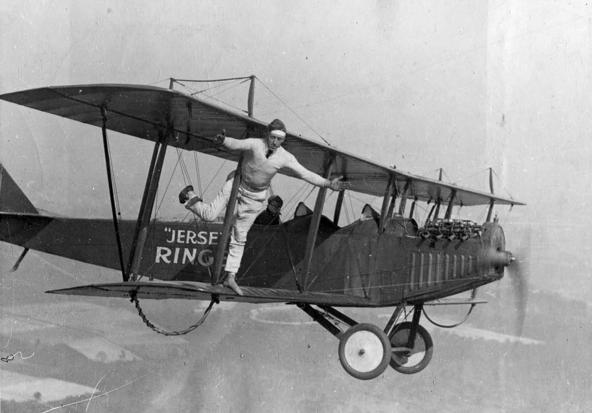 A wing walker stands on one leg on the wing of a Curtiss 'Flying Jenny' biplane in the air above New Jersey, 1920.