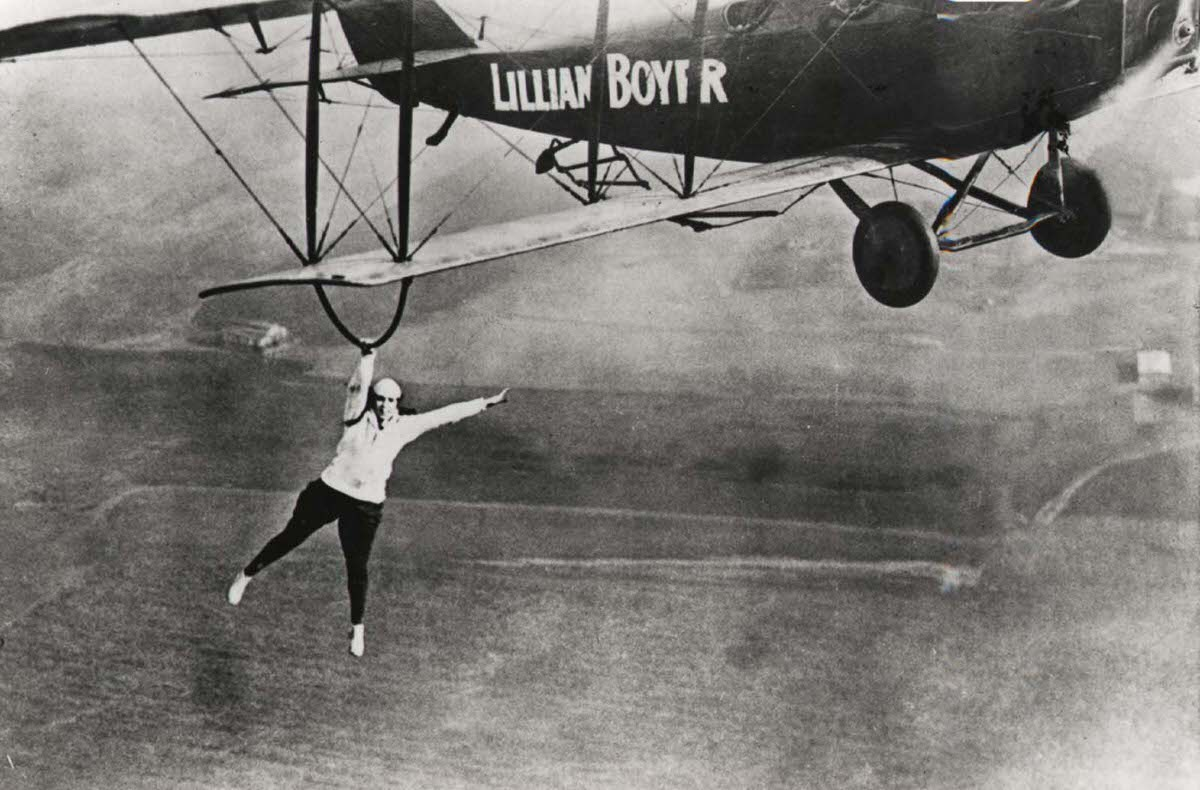 Famous wing walker Lillian Boyer dangles from the wing of a biplane, 1922.