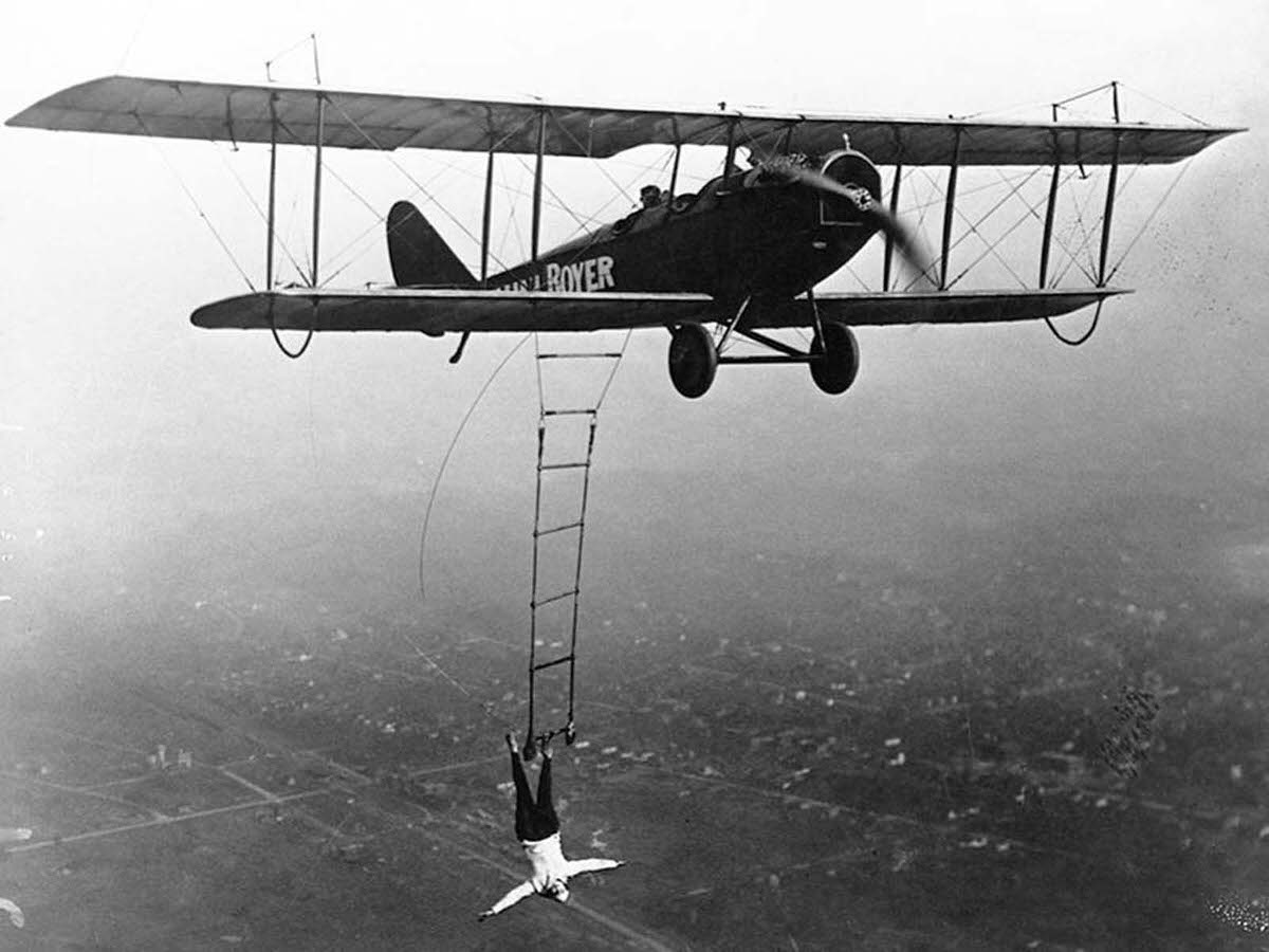 Lillian Boyer hanging from right wing boom using her right hand, 1920s.