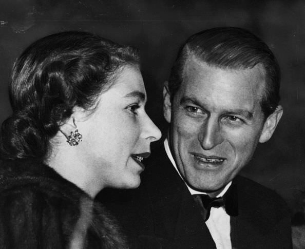 The Queen and Prince Philip talk together in the royal box at a performance of Bertram Mills Circus in London, 1952.