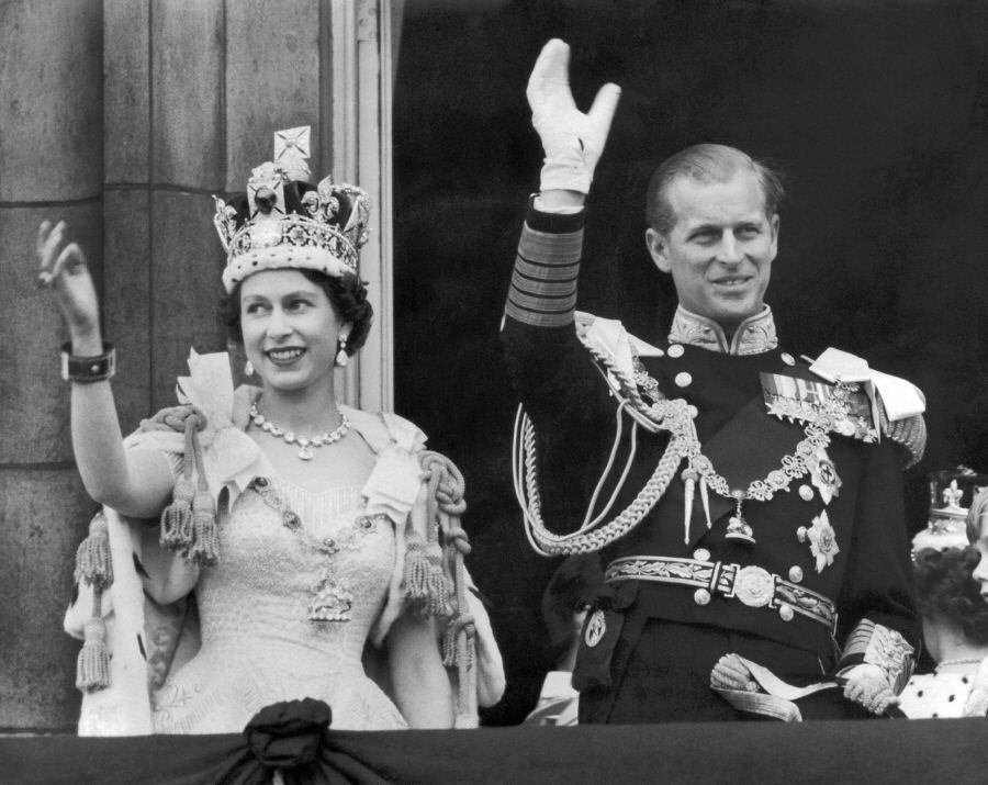 The Queen and Duke of Edinburgh wave from the famous balcony of Buckingham Palace following Elizabeth's coronation, 1953.