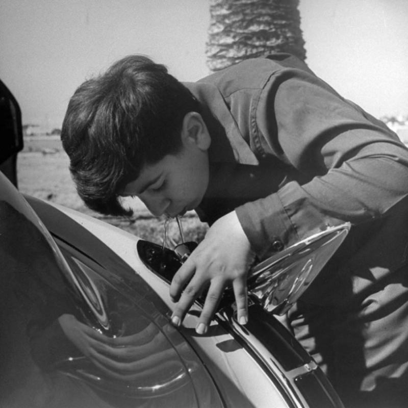 A boy drinks from a water fountain that Louis Mattar installed in his 1947 Cadillac.