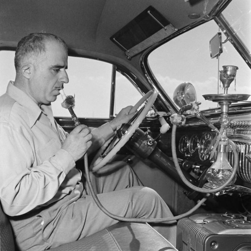 Louis Mattar enjoys a pull on the water pipe he installed in his heavily modified 1947 Cadillac.
