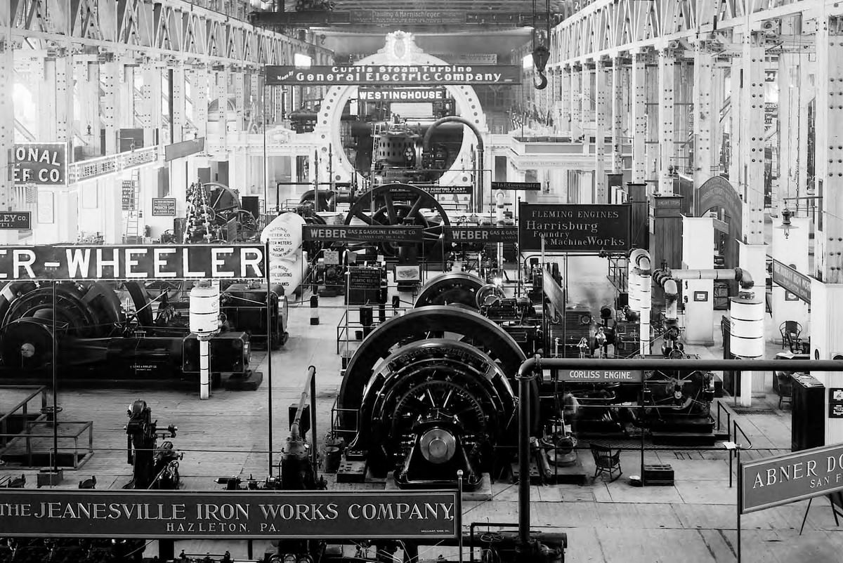 A view of the Allis-Chalmers exhibit in the Palace of Machinery shows exhibits from companies such as Jeanesville Iron Works, Crocker-Wheeler, Doble Abner, Harrisburg Foundry, General Electric, and Westinghouse.