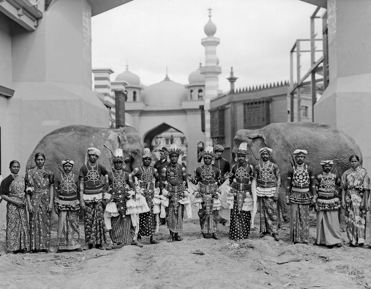 Sinhalese dancers from the Mysterious Asia concession pose with elephants on the Pike.