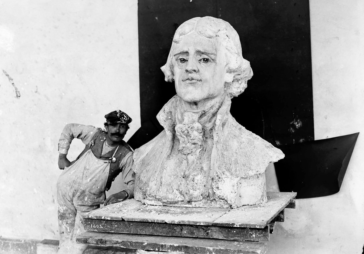 A craftsman stands by a bust of Thomas Jefferson, the model for the statue by Charles Grafly installed at the Louisiana Purchase Exposition.