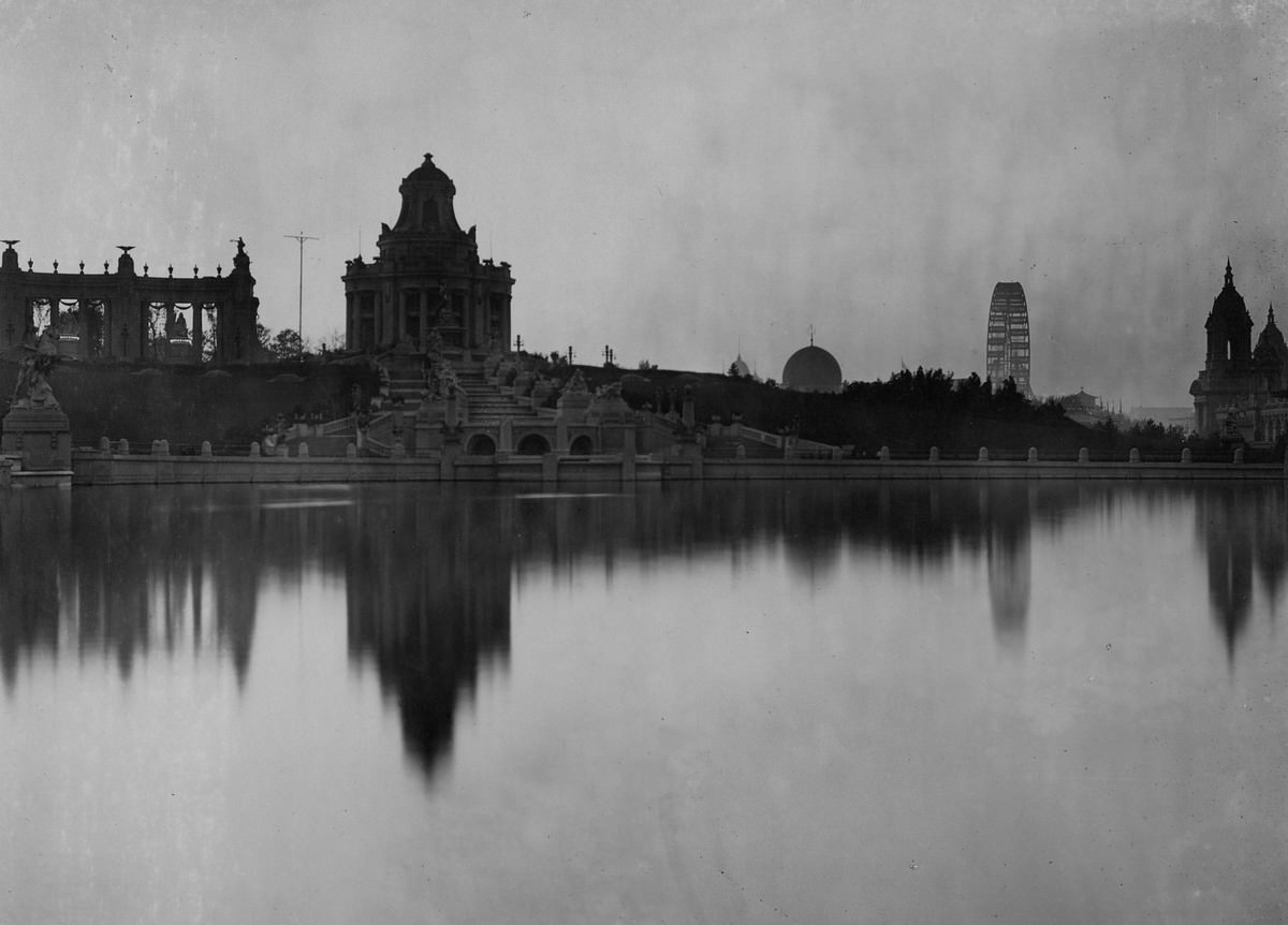 """At Sunset."""" A view across the Grand Basin at the 1904 World's Fair toward the West Restaurant pavilion and the Ferris wheel"""