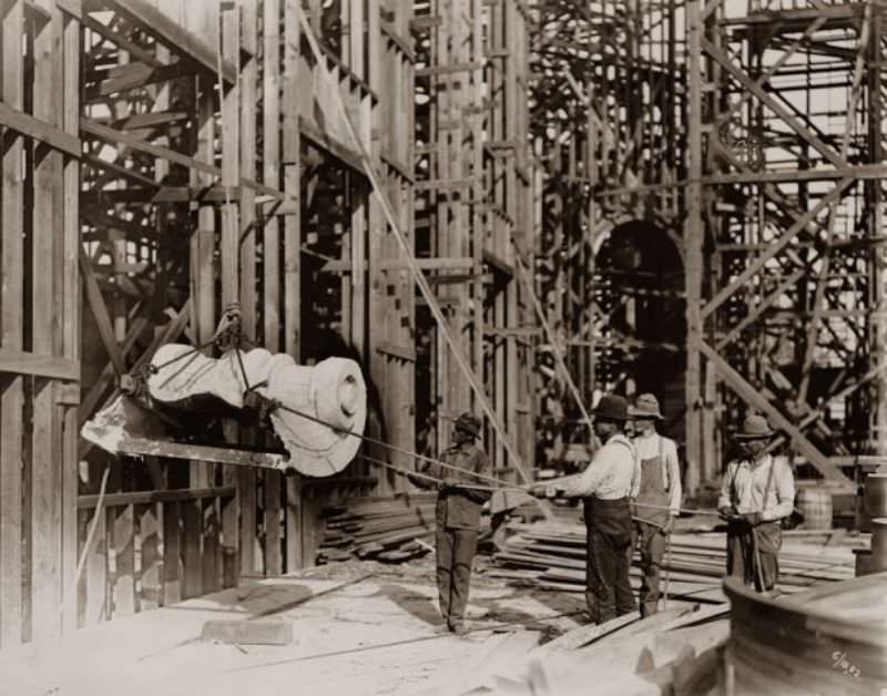 Workers hoisting the first piece of staff onto the Palace of Varied Industries for the 1904 World's Fair, 1902