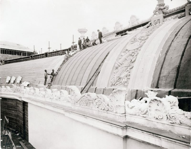 Workers preparing the roof of the Palace of Liberal Arts for placement of staff during construction for the 1904 World's Fair, 1904