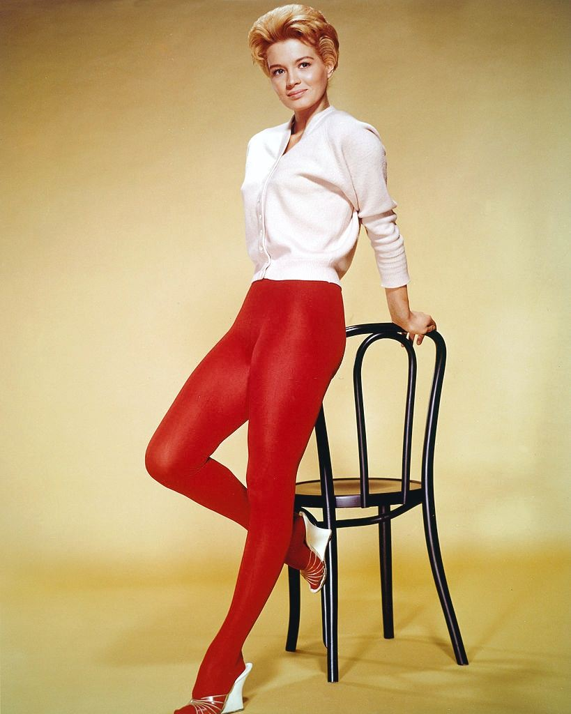 Angie Dickinson wearing a white cardigan and red tights, 1955.
