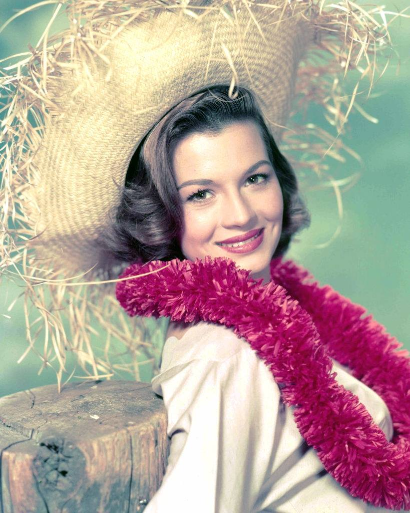 Angie Dickinson wearing a pink garland and a straw hat, 1955.