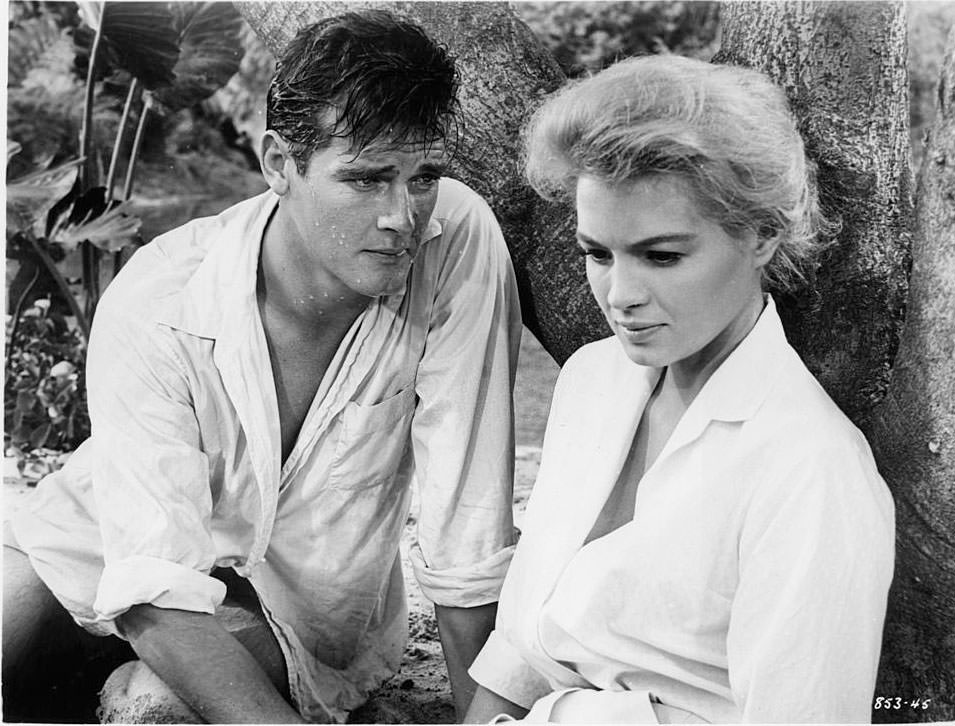 Roger Moore leaning towards Angie Dickinson in a scene from the film 'The Sins Of Rachel Cade', 1958.