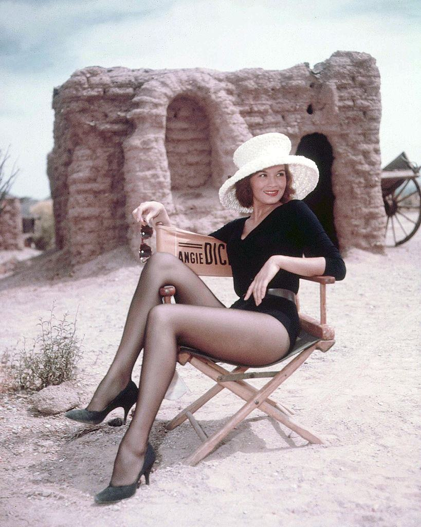 Angie Dickinson wearing a black long-sleeved leotard and a white wide brimmed hat, relaxing in a director's chair, on the set of 'Rio Bravo', 1959.