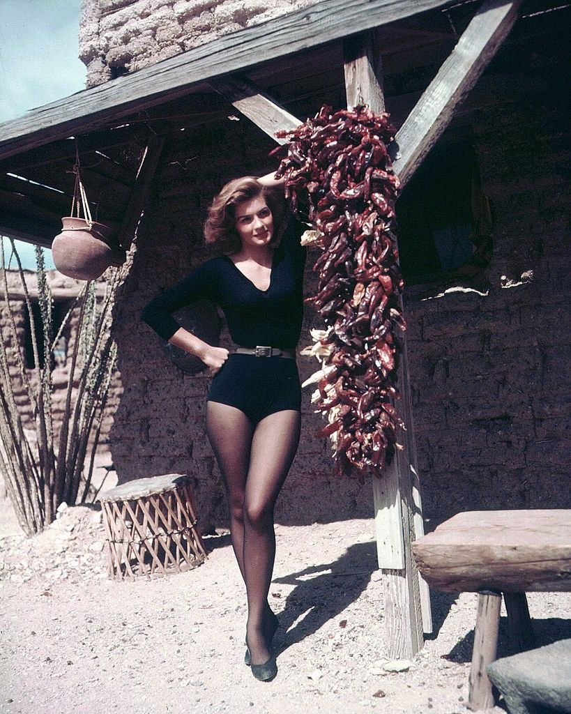 Angie Dickinson posing beside a bundle of dried chillies hanging on the set of 'Rio Bravo', 1959.