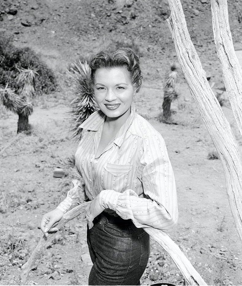Angie Dickinson miles as she poses outside on the set on an episode of 'Schlitz Playhouse of Stars' entitled 'Moment of Vengeance,' June 20, 1956.