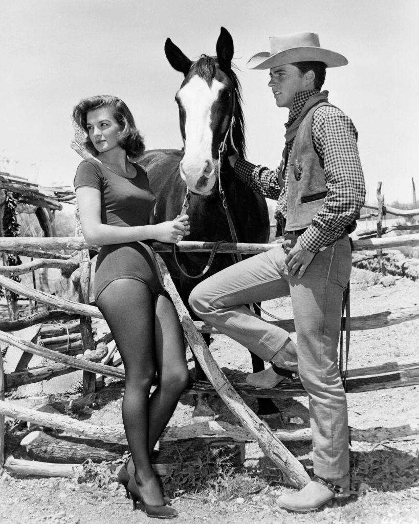 Angie Dickinson  hold a horse in a scene from the film 'Rio Bravo' with Ricky Nelson, 1959.