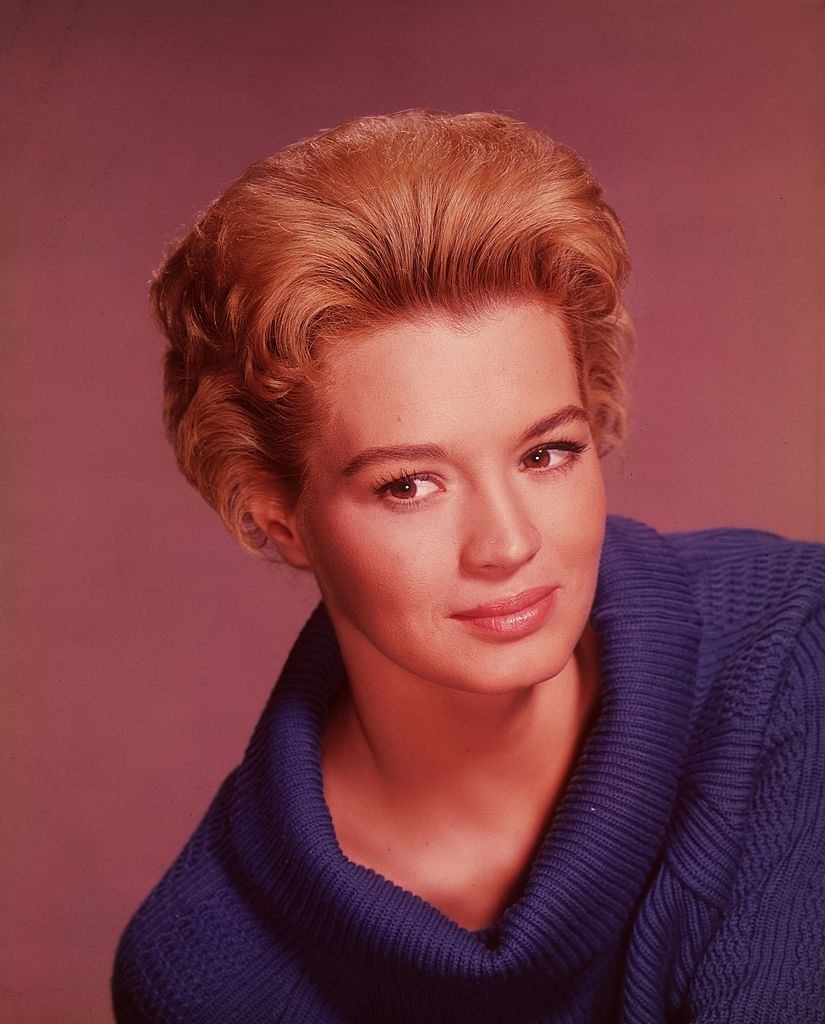 Angie Dickinson smiling in a blue cowl-necked sweater, 1960.