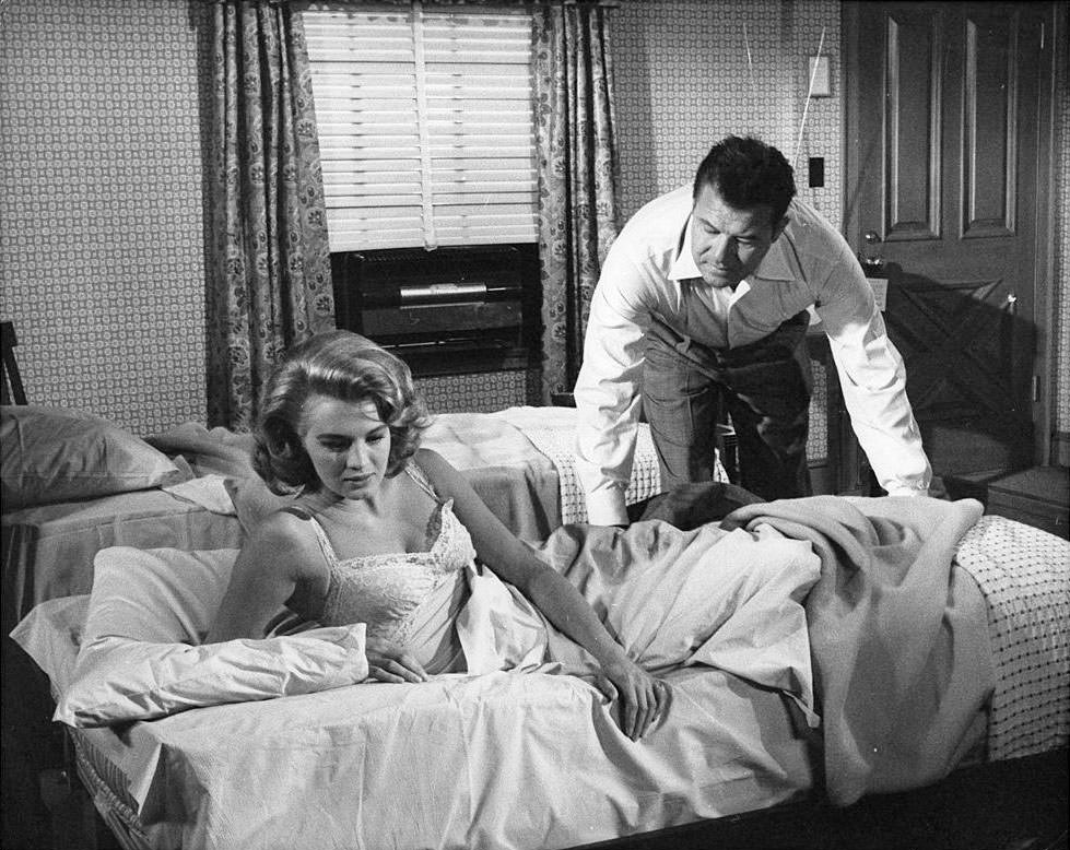 Angie Dickinson and Jack Carson in a motel room scene from the film 'The Bramble Bush', 1960.