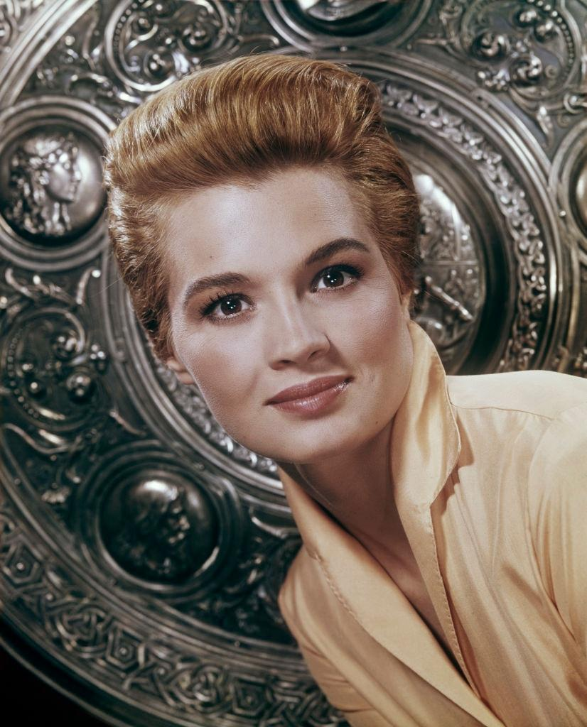 Angie Dickinson in front of an embossed shield, 1960.