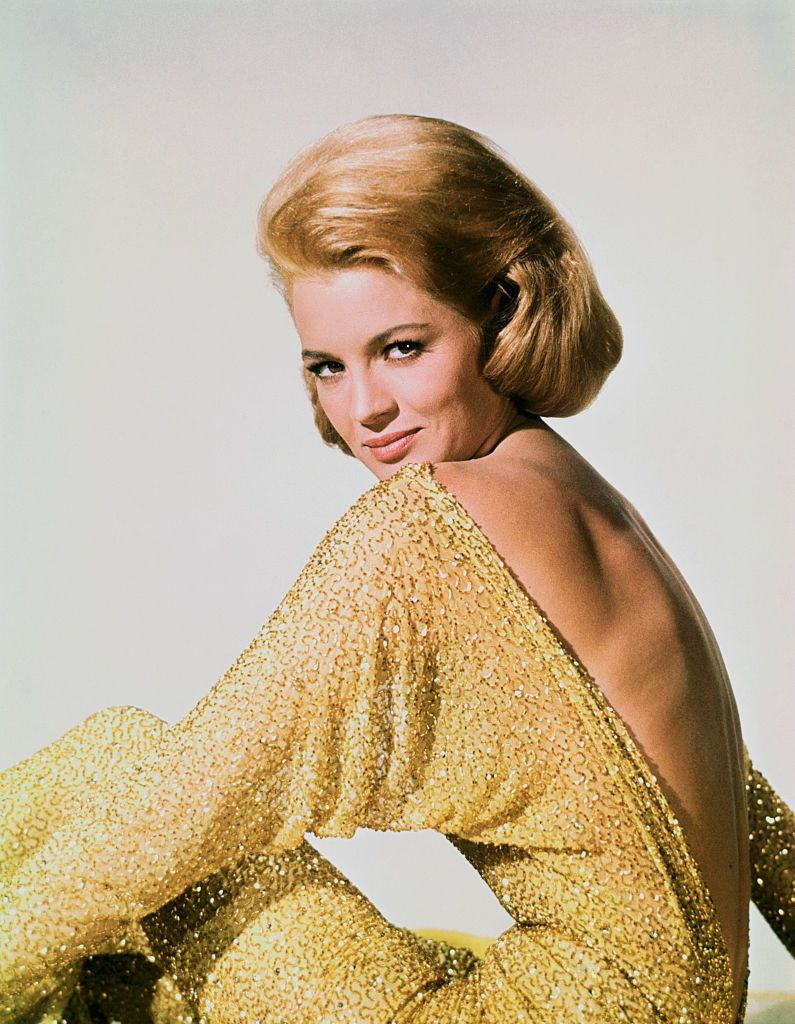 Angie Dickinson in backless yellow glittering dress, 1960.