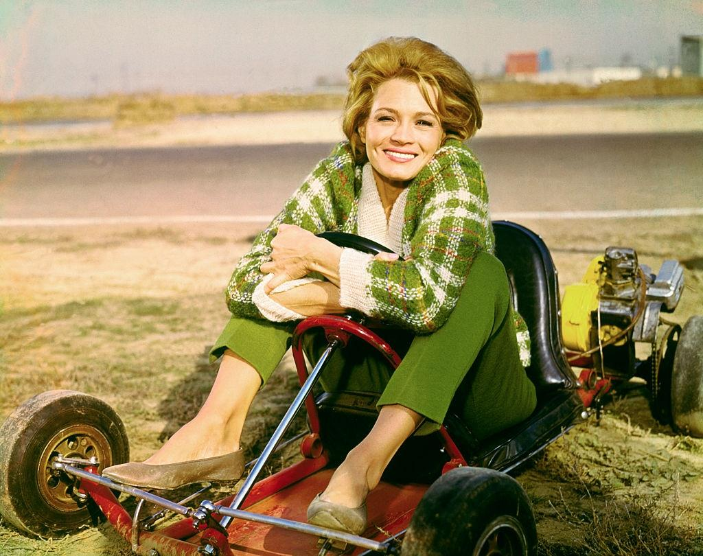 Angie Dickinson sitting in go-cart, 1960.
