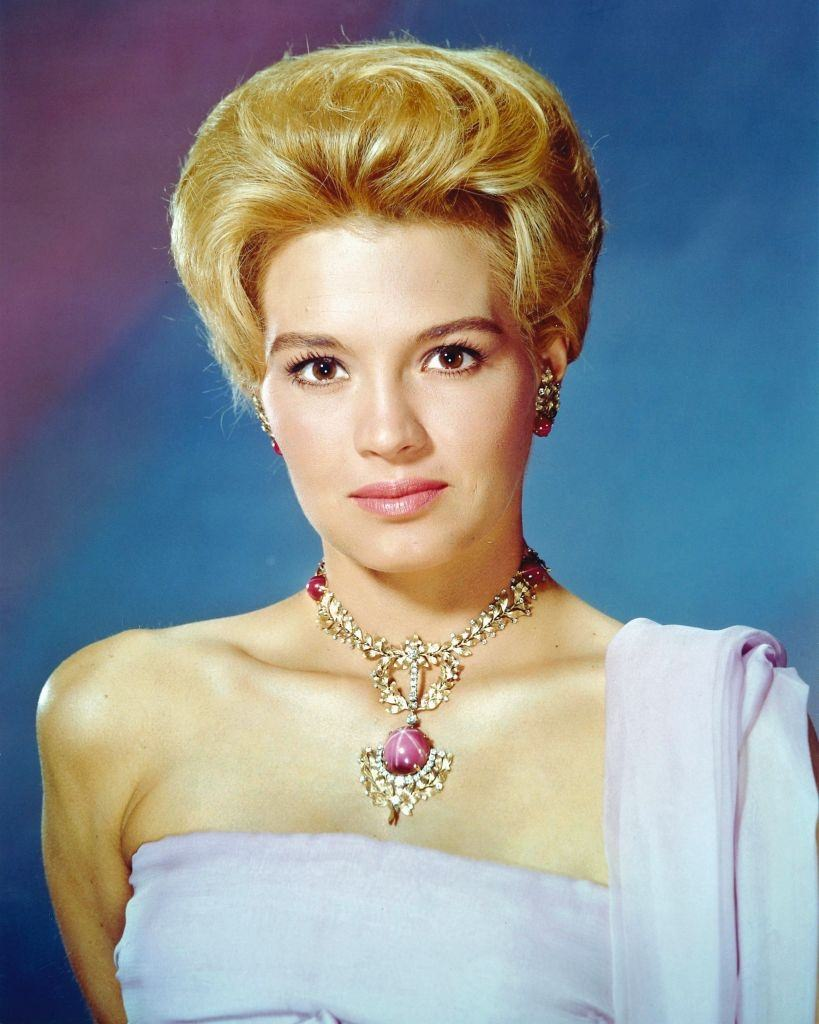 Angie Dickinson wearing a shoulderless gown and necklace with ornate pendant, 1960.