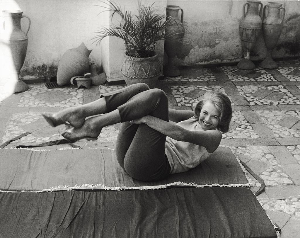 Angie Dickinson moving her legs to her chest lying on a mat on a terrace, 1961.