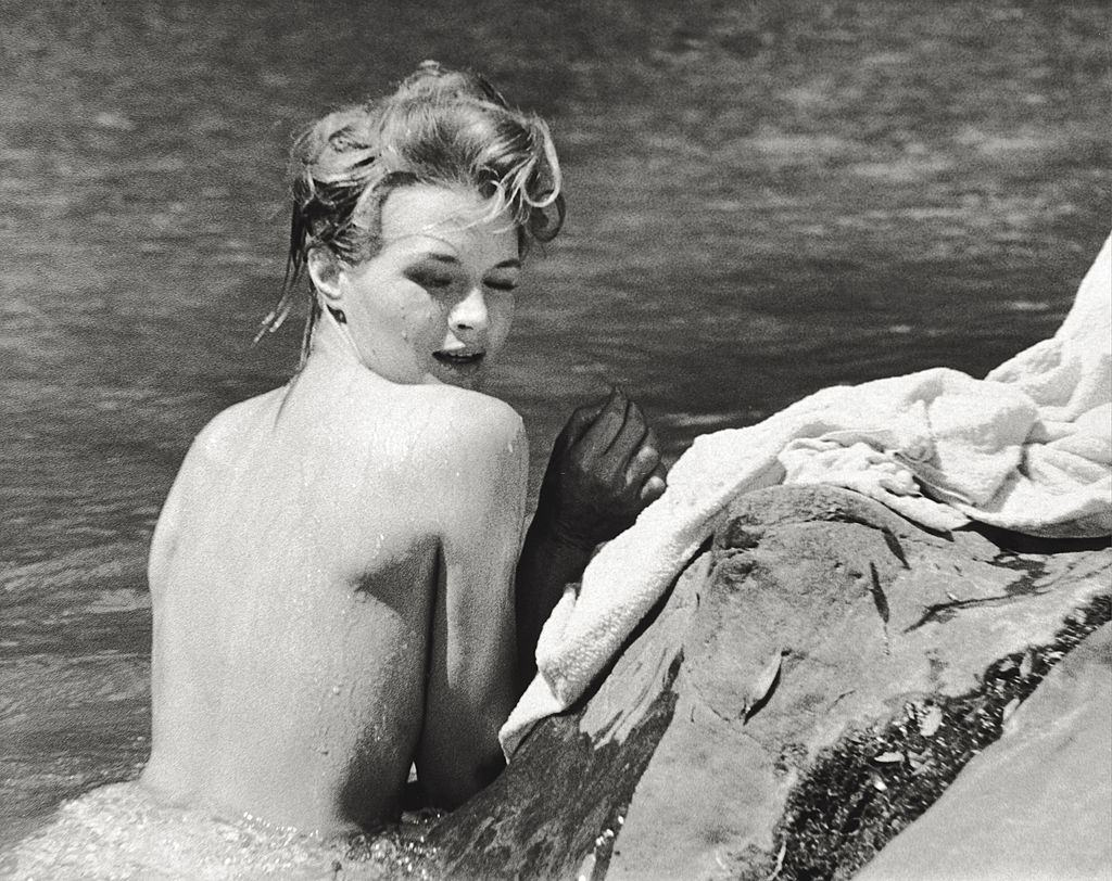 Angie Dickinson taking a bath leaning on a cliff., 1961.