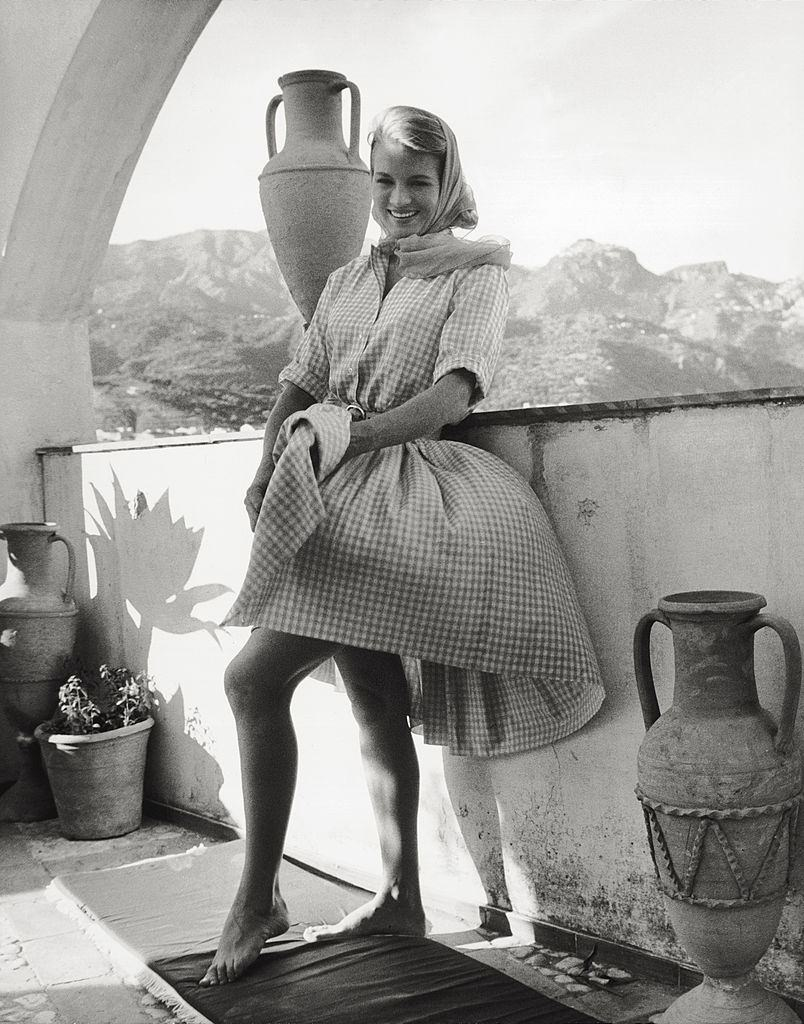 Angie Dickinson smiling while the wind whips up her dress on a terrac, 1961.