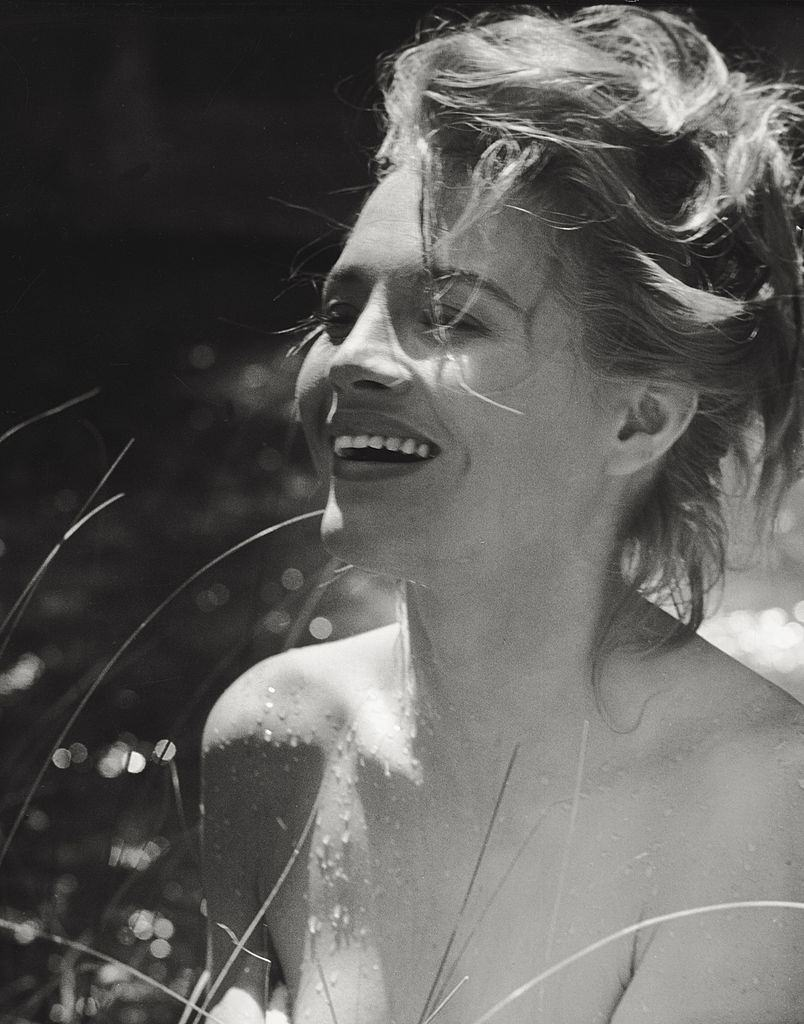 Angie Dickinson posing laughing after swimming. 1961