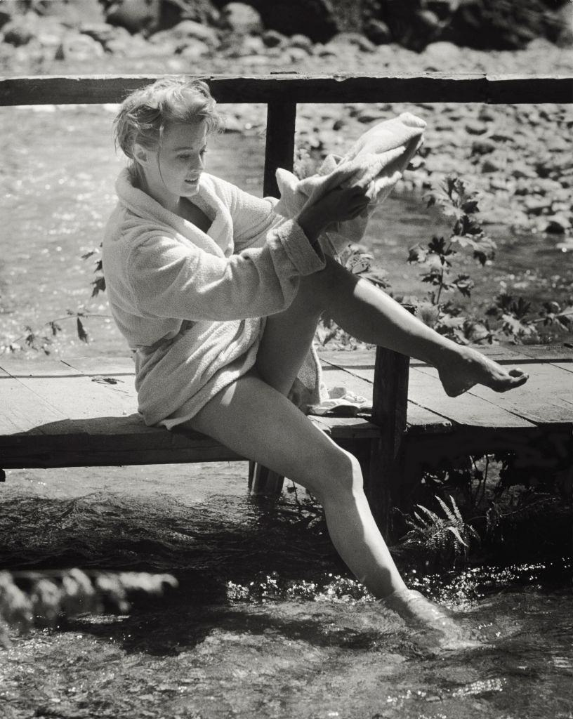 Angie Dickinson drying herself with a bathrobe after swimming, 1961.