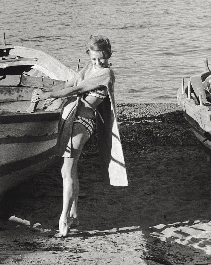 Angie Dickinson posing on the beach next to a rowing boat, 1961.