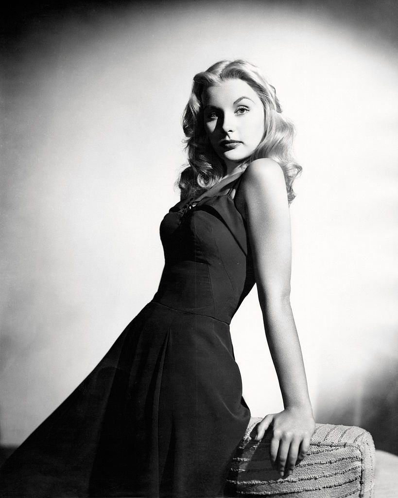 Barbara Payton leaning by the sofa, 1950.