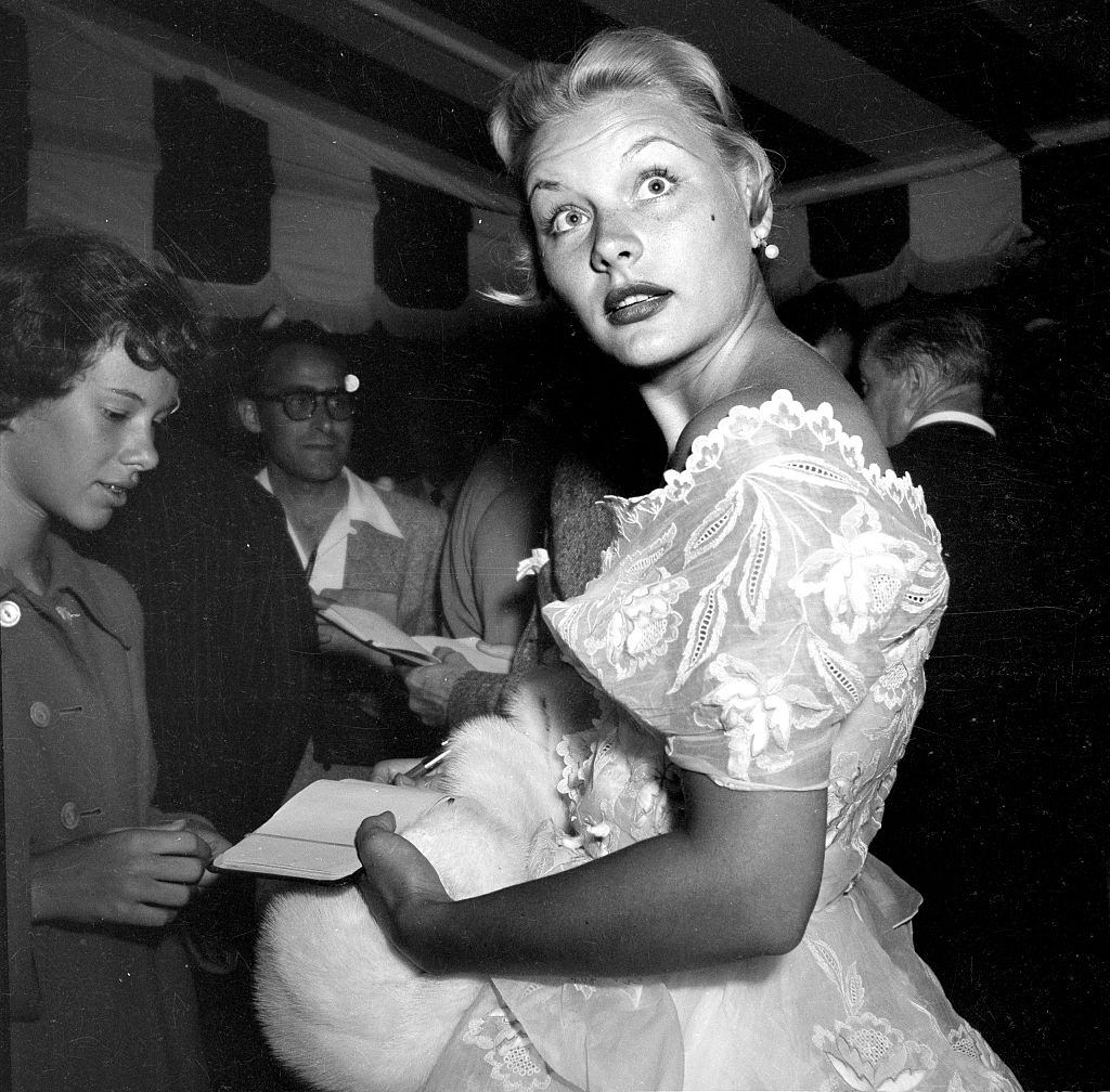 Barbara Payton signs autographs for fans outside Mocambo, 1951.